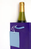 Wine Gift. Bottle of white wine in gift bag with gift tag showing Stock Image