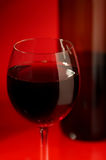 Wine in a glass. The big glass of red wine and bottle on a red background Stock Photo