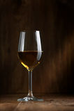 Wine in a glass. The big glass of white wine on a dark background Royalty Free Stock Images