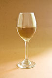 Wine glass. White wine on gold color background Royalty Free Stock Photo