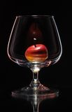 Wine glass. Small apple in the wine glass standing on a mirror in reflected light Royalty Free Stock Photos