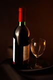 Wine and glass. Bottle of red wine and glass on black surface stock image