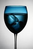 Wine glass. An isolated blue wine glass with ice water Stock Image