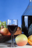 Wine glass. Over a blue bright background with fruits Stock Images