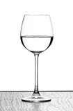 Wine glass. One wine glass in backlight on white contrast background royalty free stock photography
