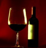 Wine and glass. Against a red backdrop Royalty Free Stock Image