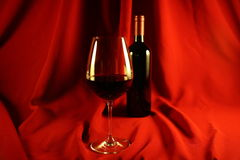 Wine and glass. Against a red backdrop Royalty Free Stock Photos