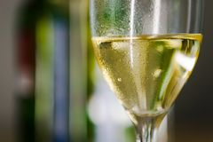 Wine Glass. Wine in a glass. Bottles in the background out of focus royalty free stock image