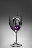 Wine Glass. A purple die splashing in a wine glass Stock Photography