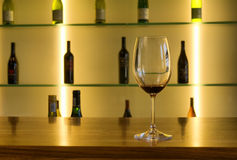 Wine glass against array of bottles Royalty Free Stock Image