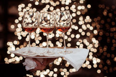 Wine glass against christmas lights decoration Royalty Free Stock Photography