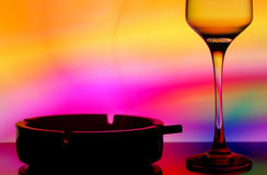 Wine glass and ashtray. Still life with a wine glass, burning cigarette in the ashtray on colorful backdrop Royalty Free Stock Image