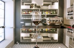 Wine glass on bar counter with reflections at contemporary design style restaurant. Modern drinking cafe with bottles. Wine glass on bar counter with reflections royalty free stock photo