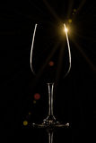 Wine glass on black background with sun flare.  stock photography