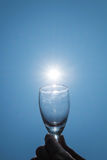 Wine glass on blue sky with sun lens flare effects Royalty Free Stock Photography