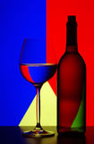 Wine glass and bottle. Side view of wine glass and bottle with colorful abstract background Royalty Free Stock Photography