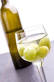 Wine glass and a bottle on background Stock Image