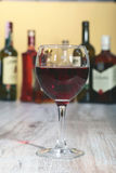 Wine glass and Bottle on a black mirror background Stock Photos