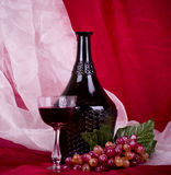 Wine in glass and bottle with red grape Royalty Free Stock Photo