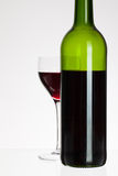 Wine glass and bottle with red wine Stock Photos