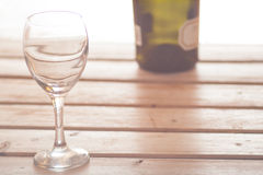 Wine glass with bottle on wooden background dreamy loo Royalty Free Stock Photography