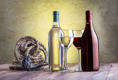 Wine glass with bottles and tobacco pipe. Still life with wine glass, bottles, rope and tobacco pipe on stucco background Stock Photography