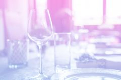 Wine glass at celebration and dining table setting with flowers decorations on light pink blue gradient background. Abstract defocused blur background stock image