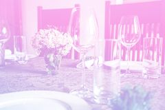 Wine glass at celebration and dining table setting with flowers decorations on light pink blue gradient background. Abstract defocused blur background stock images