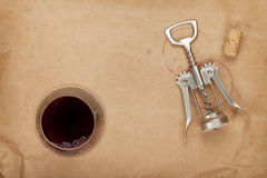 Wine glass, cork and corkscrew with red wine stains. On brown paper background Royalty Free Stock Photos