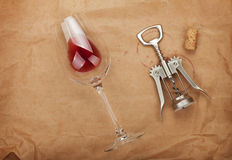 Wine glass, cork and corkscrew with red wine stains. On brown paper background Royalty Free Stock Images