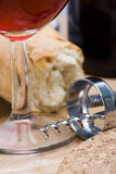 Wine glass and corkscrew. Detail of a wine glass with silver corkscrew and bread in background stock photography