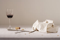 Wine glass cutlery dish cloth on messy table Royalty Free Stock Photo