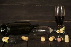 Wine in a glass an empty bottle of figs on a dark wooden background. A glass of wine on a wooden table. stock photo