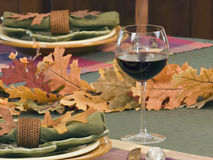 Wine glass on fall table. Decorative fall table setting with focus on red wine in glass stock photo