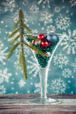 Wine glass filled with christmas tree balls and glass beads. Royalty Free Stock Photography
