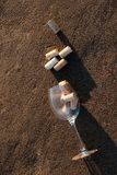 Wine glass filled with cork stoppers in the sand on the beach. Wine glass filled with cork stoppers lies on a sandy beach stock photo