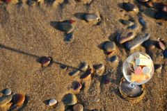 Wine glass with cork stoppers on the beach. Wine glass filled with cork stoppers standing on the sand on the beach royalty free stock photo