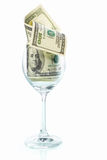 Wine glass filled with dollar bills Royalty Free Stock Images