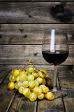 Wine glass and fresh bunch of white grapes on antique wooden bac Royalty Free Stock Photography