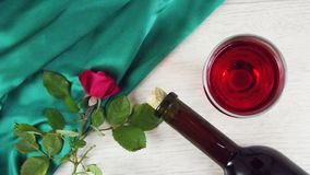 Wine in a glass and a fresh rose. Wine in a glass and a fresh rose on a green napkin stock photo