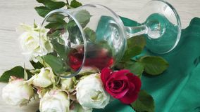 Wine in a glass and a fresh rose. stock image