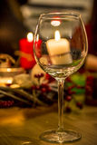 Wine glass in front of candles royalty free stock image