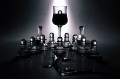Wine glass and glass chess pieces Stock Images