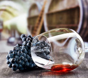 Wine glass with grape on wooden table Stock Image