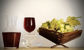 Wine, glass, grapes. A carafe of red wine with appropriate sommelier glasses and a basket of grapes - vignetting added Royalty Free Stock Image