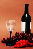 Wine glass, grapes and bottle. On  biege background Royalty Free Stock Image