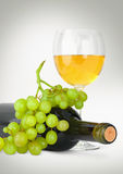 Wine in glass with grapes and bottle on grey Stock Photography
