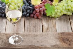 Wine glass and grapes. On wooden table. With space for your text Royalty Free Stock Photography