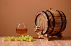 Wine in a glass grapes and wooden barrel Royalty Free Stock Image