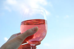 Wine Glass. A hand holding a glass of rose wine to the sky Stock Images